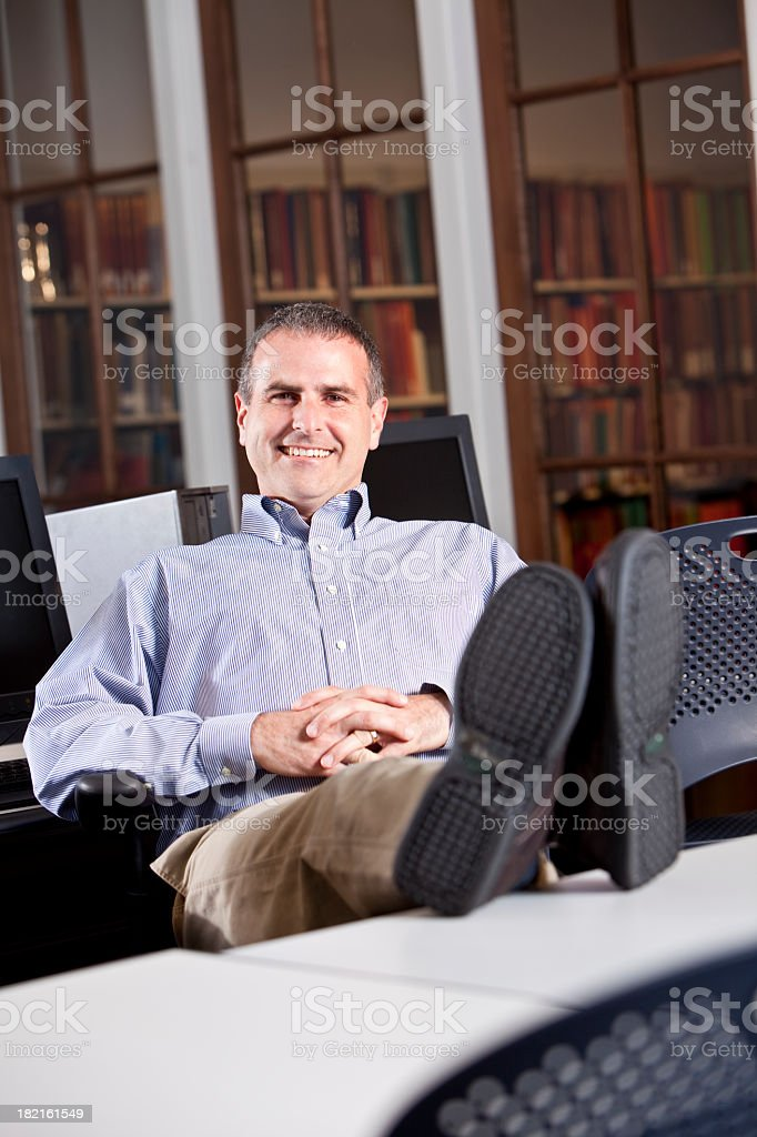 Relaxed man in computer lab with feet up on desk stock photo