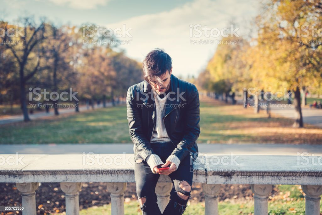 Relaxed man in the park texting stock photo