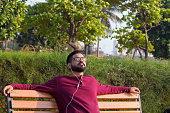 Relaxed young man with closed eyes listening to music at park bench