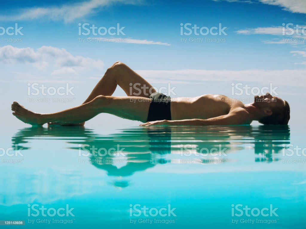 Relaxed Man Lying Reflecting on Infinity Pool royalty-free stock photo