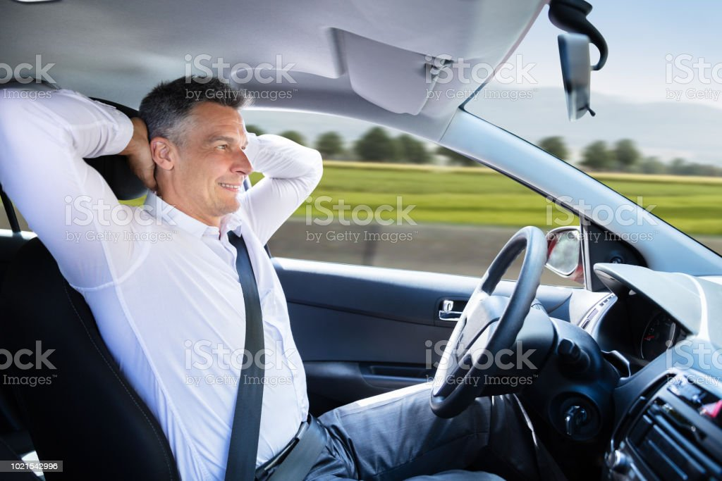 Relaxed Man Sitting In Self Driving Car stock photo