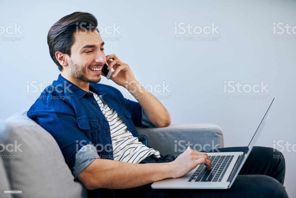 Relaxed man sitting on sofa talking on the phone and typing on his laptop stock photo