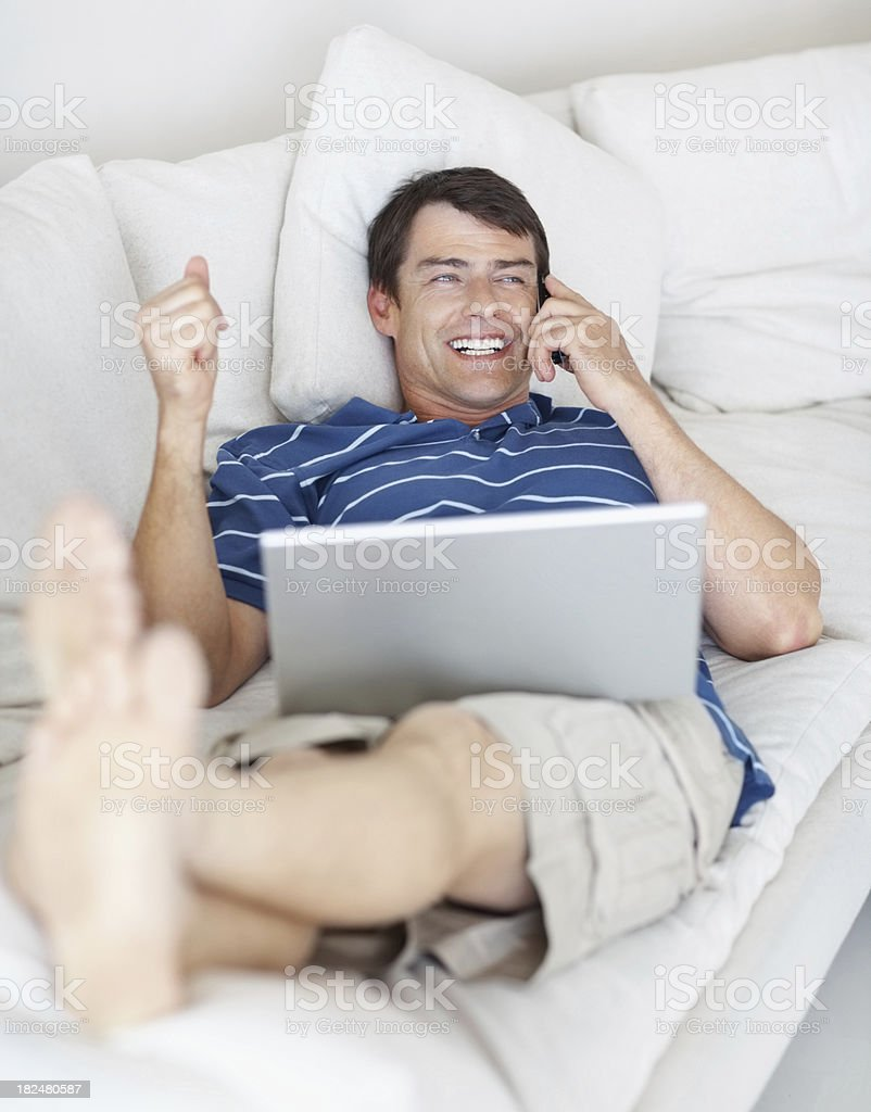Relaxed man using cellphone and laptop on couch royalty-free stock photo