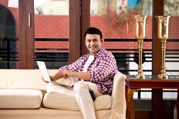 Entspannter Mann mit Laptop, während er auf dem Sofa sitzt – Foto