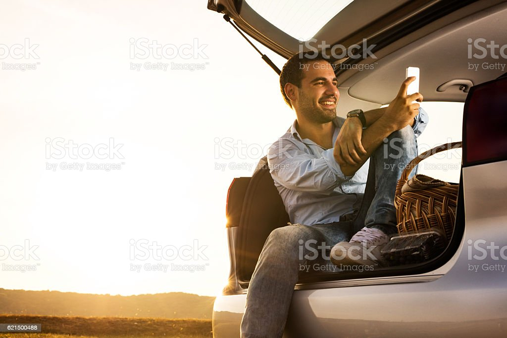 Relaxed man using smart phone in car trunk at sunset. stock photo