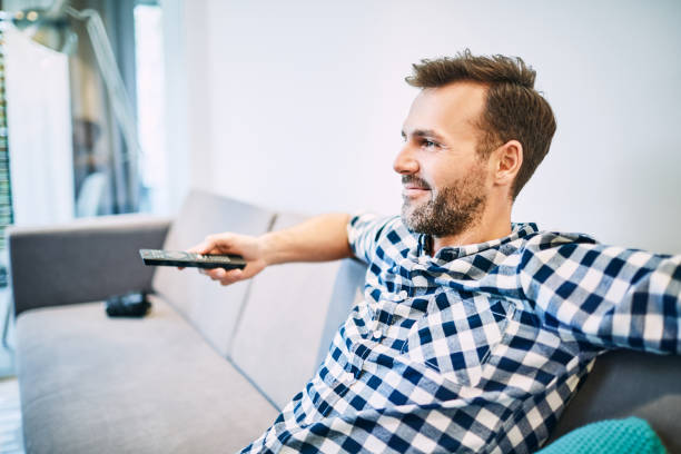 Relaxed man watching tv at living room stock photo