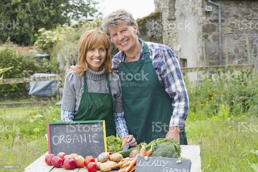 Relaxed mature couple selling vegetables royalty-free stock photo