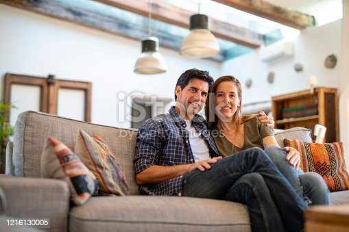 Low angle close-up of Spanish couple in early 40s sitting close together on sofa in family home and smiling at camera.