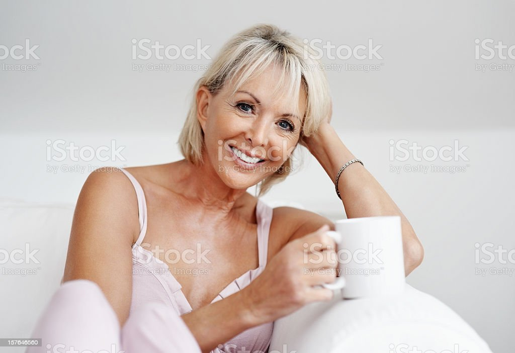 Relaxed mature female holding a cup of tea or coffee royalty-free stock photo