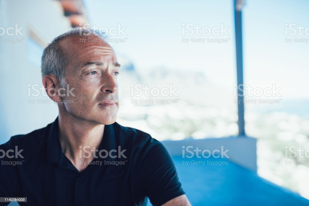 Confident mature man sitting on chair on balcony in a villa in camps...