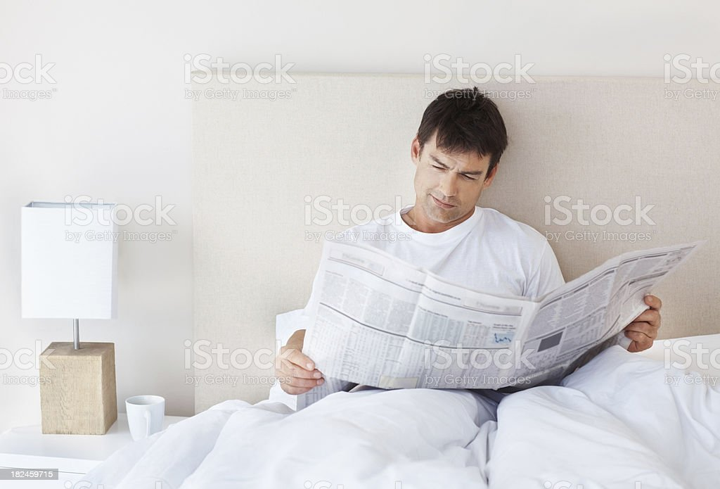 Relaxed mature man reading a newspaper in bed royalty-free stock photo