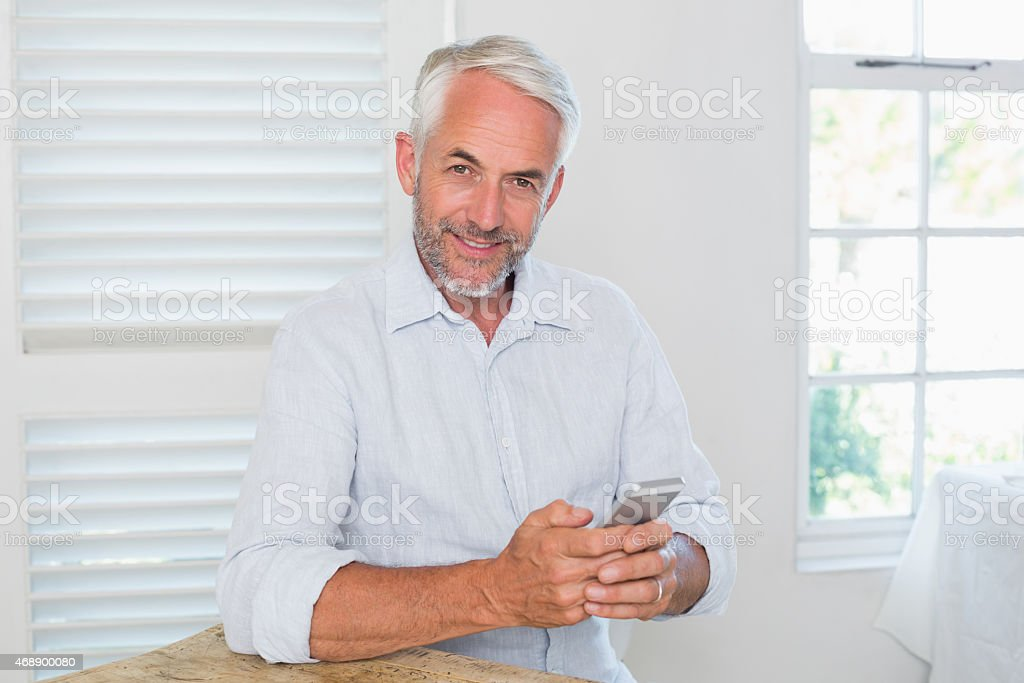 Relaxed mature man text messaging at home stock photo