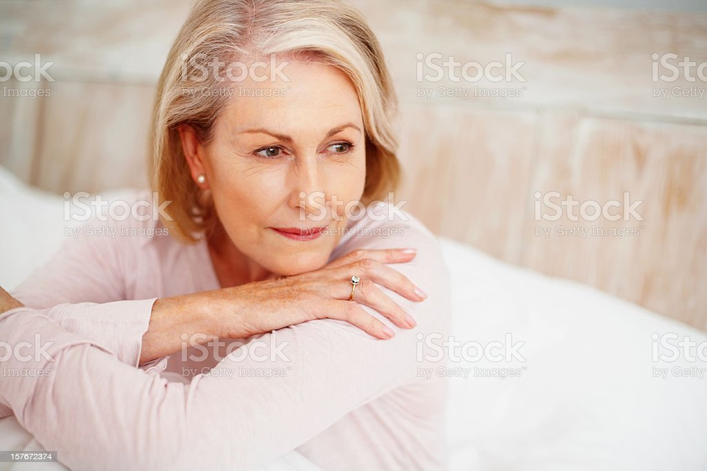 Relaxed mature woman in bed looking away royalty-free stock photo
