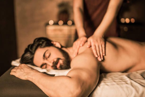 relaxed mid adult man enjoying a back massage. - massaggio foto e immagini stock