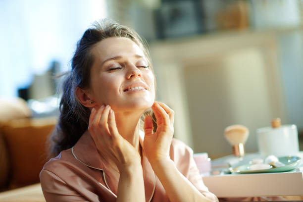 relaxed modern woman applying cream and making massage stock photo