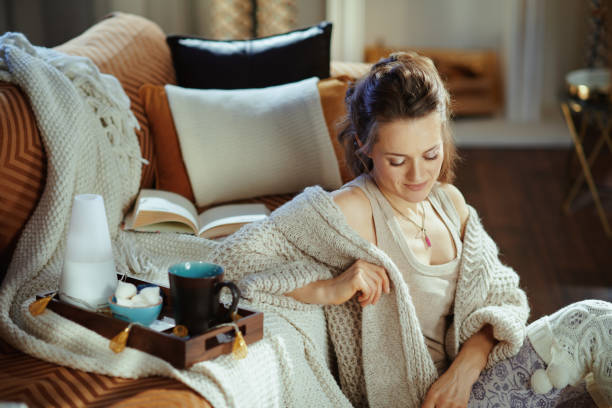 relaxed modern woman sitting near couch in modern living room stock photo