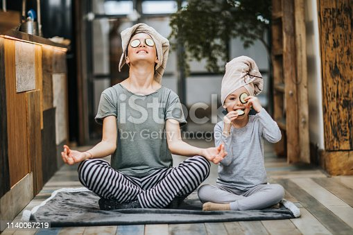 Mother and little girl taking care of their bodies in the morning while doing Yoga meditation exercises at home. Girl is cheating while eating cucumbers from her eyes and looking at camera.