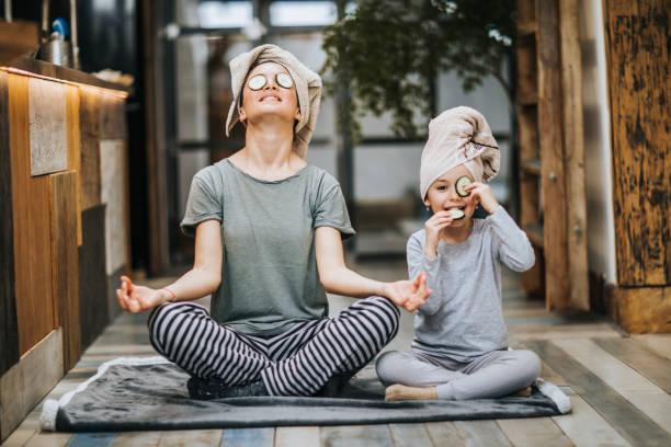 relajada madre e hija ejercitando yoga en la mañana en casa. - hija fotografías e imágenes de stock