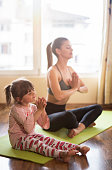 istock Relaxed mother and daughter exercising Yoga in the morning at home. 1142601301