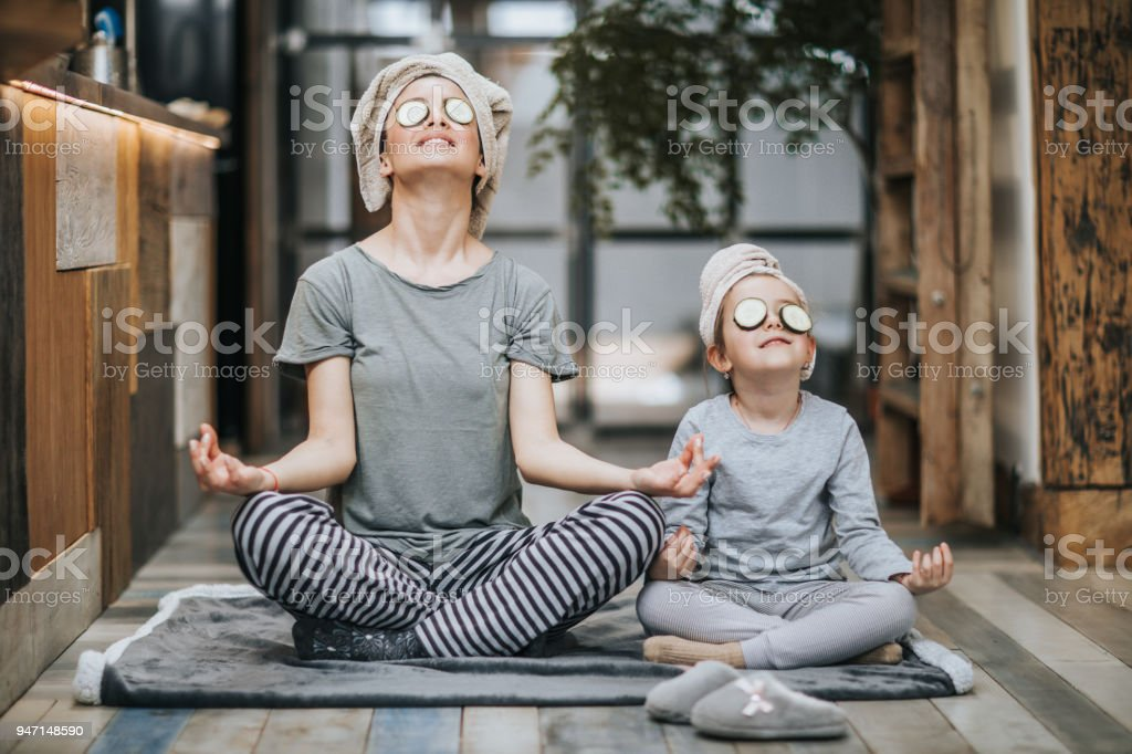 Relaxed mother and daughter exercising Yoga in the morning at home. stock photo