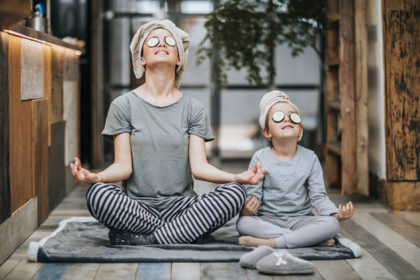 Relaxed mother and daughter exercising Yoga in the morning at home. - foto stock