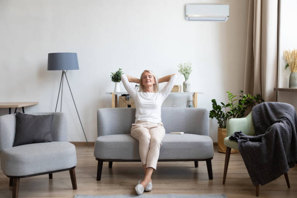 Relaxed older woman sitting on couch in air conditioner room Relaxed satisfied older woman sitting leaning back on couch in air conditioner room, happy peaceful mature female with hands behind head resting on sofa at home, enjoying fresh air, breathing comfortable stock pictures, royalty-free photos & images