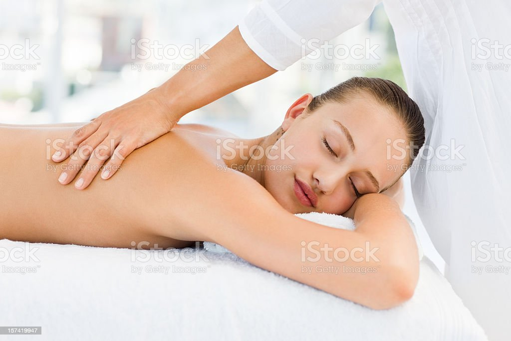 Relaxed pretty woman receiving back massage stock photo
