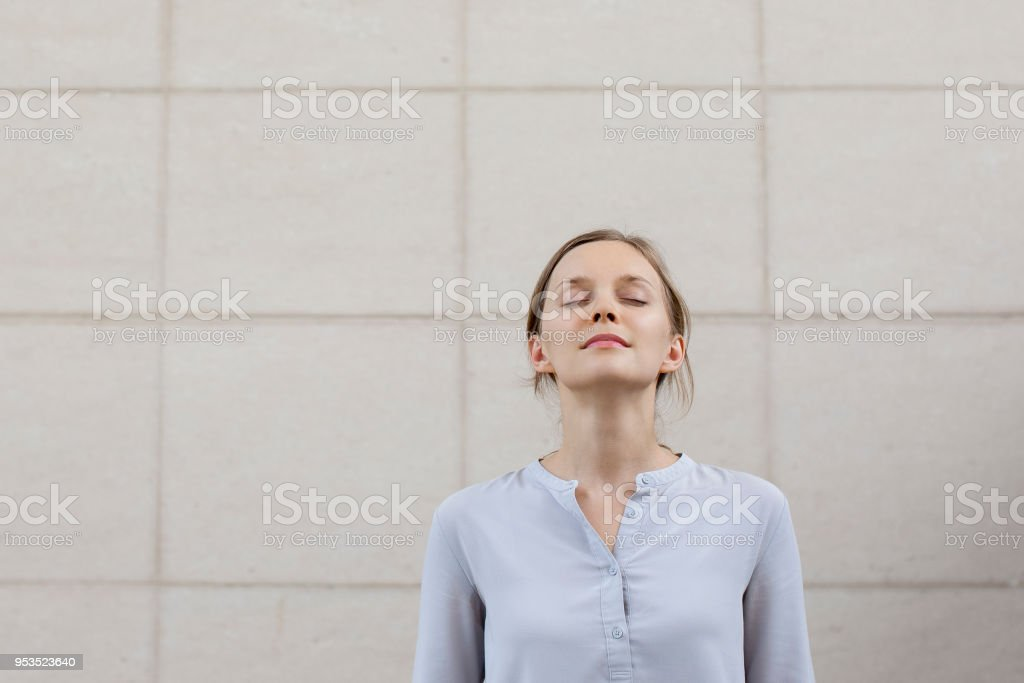 Relaxed pretty young woman standing at wall outdoors Relaxed pretty young woman standing at wall outdoors. Female student or business woman relaxing with her eyes closed. Serenity concept. Front closeup view. Adult Stock Photo