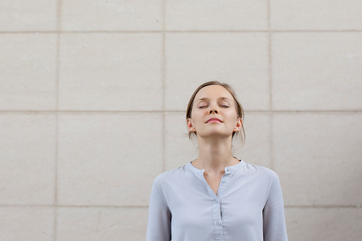 Relaxed Pretty Young Woman Standing At Wall Outdoors Stock Photo - Download Image Now