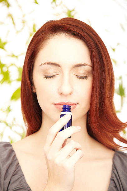 relaxed redhead woman smelling essential oil with eyes closed - aromatherapy stock photos and pictures