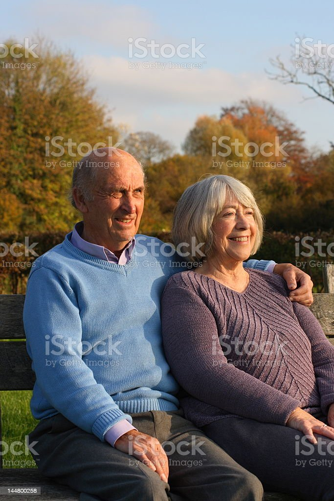 Relaxed senior couple on a park bench royalty-free stock photo