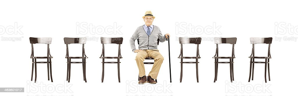 Relaxed senior gentleman sitting on a wooden chair stock photo