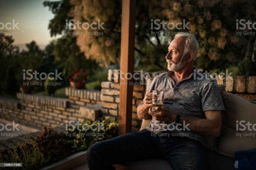Pensive mature man drinking beer while relaxing in his back yard.