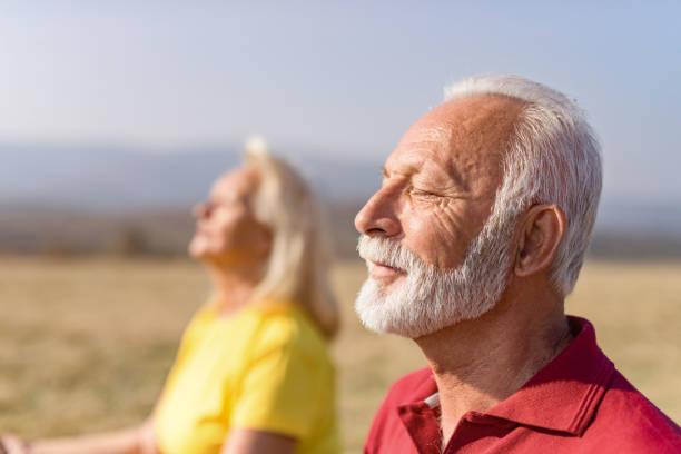 relaxed senior man meditating in nature with his wife. - meditation stock pictures, royalty-free photos & images