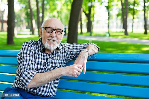 Smiling senior man outdoors. Elderly man in eyeglasses, wearing casual clothes, sitting on the bench in the park, posing on camera, copy space