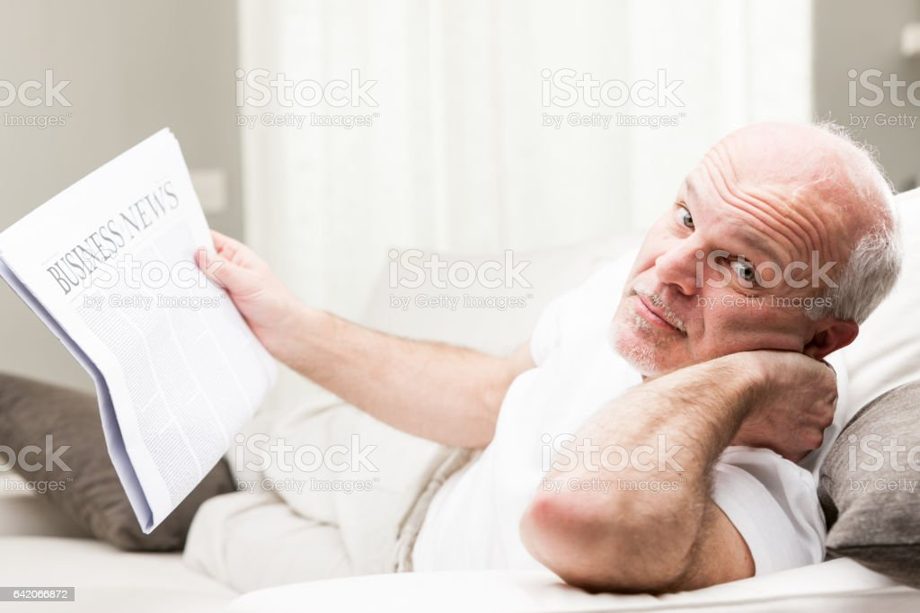 relaxed senior man reading business news stock photo