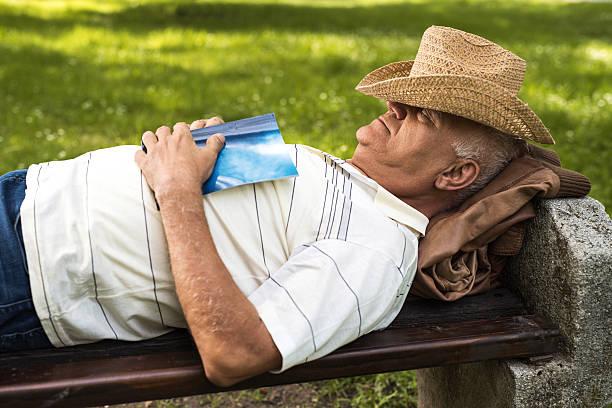 Lässig Alter Mann ein Nickerchen auf einer Bank im Freien. – Foto