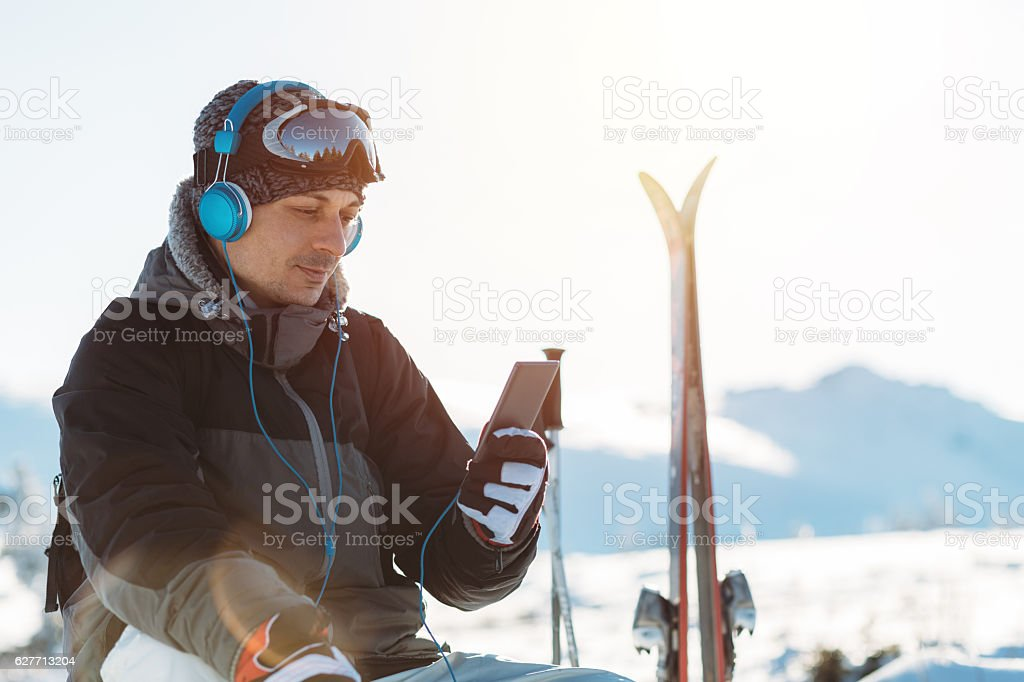 Relaxed skier with headphones on the mountain top stock photo