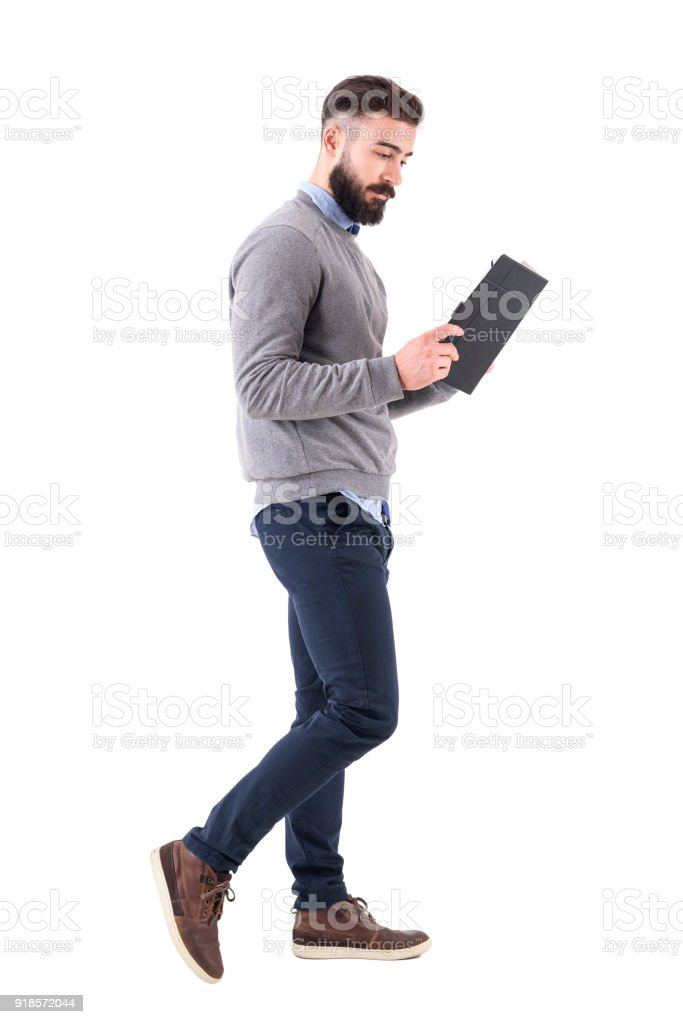 7400bf18be Relaxed smart casual businessman walking and reading notebook royalty-free  stock photo