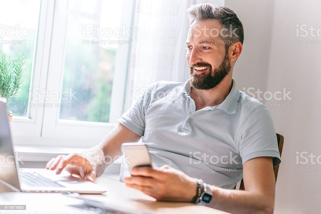 relaxed smiling beautiful bearded business man works at home office stock photo
