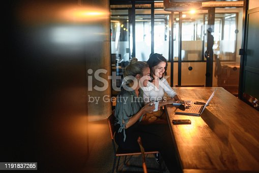 Side view of cheerful female business partners working together with coffee and laptop in dimly lit board room.