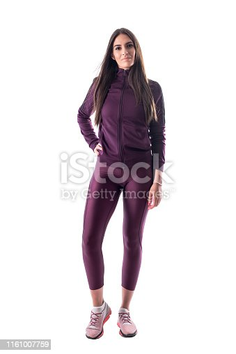 istock Relaxed smiling long hair brunette fit woman in tracksuit posing and looking at camera. 1161007759