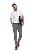 istock relaxed smiling smart casual man holding suitcase is walking 1131989080