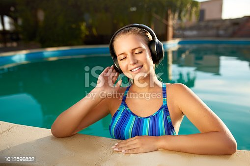 Relaxed smiling woman listening to the music with headphones bathing in swimming pool. Attractive blonde enjoys favourite song with bluetooth hi-fi headset and goosebumps on skin. Waterproof headphones with touch control and mobility concept .