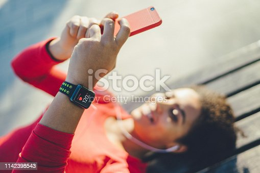 Mixed race woman lying on bench and listening to music