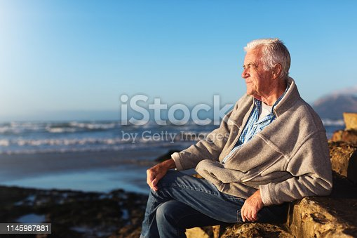 621898406istockphoto Relaxed, tanned senior man sits by the sea 1145987881