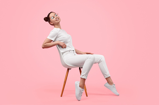 Side view of cheerful female teenager in stylish white outfit smiling and leaning back while sitting on chair against pink background