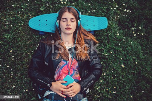 istock Relaxed teenage girl in the grass listening to music 959903066