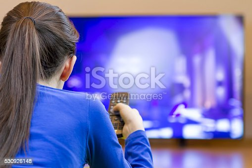 istock Relaxed teenage girl with remote control watching smart TV 530926148