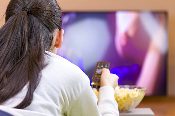 entspannt teenager-mädchen mit fernbedienung bei smart tv - jugendfilm stock-fotos und bilder